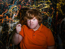Red-haired funny boy showing fig sign. Red-haired funny fat boy showing fig sign stock photo