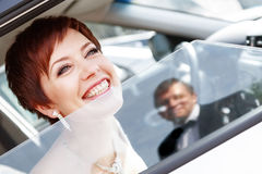 Red-haired funny bride in the car smiling groom. Woman 35 years. Wedding Royalty Free Stock Images
