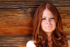 Red-haired girl. On wood wall royalty free stock images
