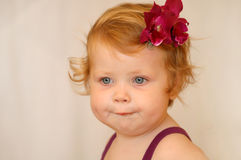 Red-haired girl. Looks toward, white background, red flower pin Stock Photo