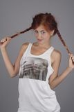 The red-haired girl. In a white vest behaves for plaits. (Small depth of sharpness royalty free stock image