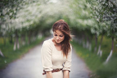 Red haired girl in apple alley on the wind. Street spring may wind alley Royalty Free Stock Images