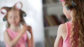 Red-haired girl applying curlers in front of mirror at home, future lady, beauty stock images