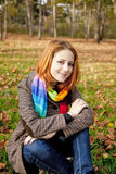 The red-haired girl in autumn leaves. Stock Images