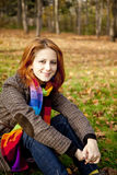 The red-haired girl in autumn leaves. Royalty Free Stock Photo