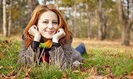 The red-haired girl in autumn leaves. Stock Photography