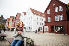 Red-haired girl on a background of colorful houses in Europe. Stock Photo