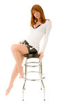 Red haired girl on a bar chair Royalty Free Stock Image