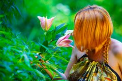 Red-haired girl and beautiful lily in the garden Royalty Free Stock Images