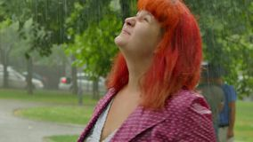 Red-haired girl becomes wet under the rain. stock footage