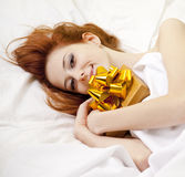 Red-haired girl in bed with gift Royalty Free Stock Image