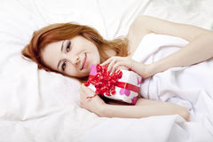 Red-haired girl in bed with gift Royalty Free Stock Photos