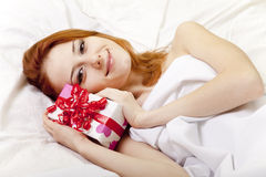 Red-haired girl in bed with gift Stock Image