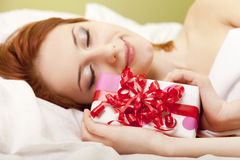 Red-haired girl in bed with gift Stock Photography