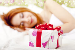 Red-haired girl in bed with gift Royalty Free Stock Photo