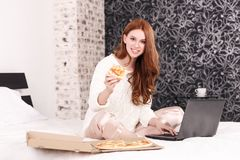 Red-haired girl on the bed working on laptop and eating pizza stock photos