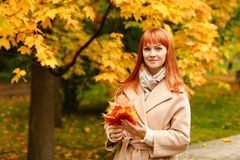 The red-haired girl in a beige coat smiles on autumn background stock photography