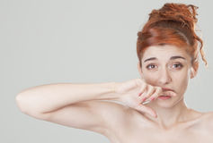 Red haired girl bites her finge Stock Images