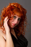 Red-haired girl in a black dress Stock Photos