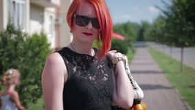 Red-haired girl in black dress standing on the sidewalk in front stock video