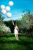 Red haired girl in a blossoming apple garden stock photos