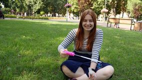 Red-haired girl blows soap bubbles in the park. She smiling and laughing summer and happiness stock video footage