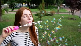 Red-haired girl blows soap bubbles in the park Slow Motion. Red-haired girl blows soap bubbles in the park She smiling and laughing summer and happiness Slow stock video footage