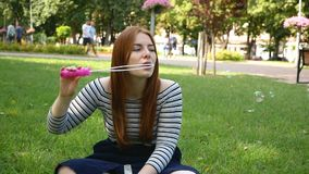 Red-haired girl blows soap bubbles in the park Slow Motion. Red-haired girl blows soap bubbles in the park She smiling and laughing summer and happiness Slow stock video