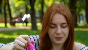 Red-haired girl blows soap bubbles in the park. She smiling and laughing summer and happiness stock video