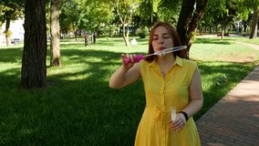 Red-haired girl blows soap bubbles in the park.yellow dress. She smiling and laughing.summer and happiness stock footage