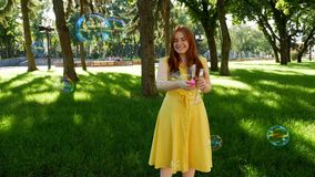 Red-haired girl blows soap bubbles in the park.yellow dress. She smiling and laughing.summer and happiness stock video