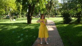 Red-haired girl blows soap bubbles in the park.yellow dress. She smiling and laughing.summer and happiness stock video footage