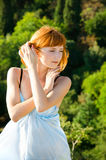 Red-haired girl in a blue dress Stock Images