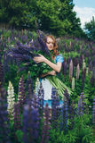 Red-haired girl in blue dress with lupines. Red-haired woman in blue dress with lupines Stock Photo