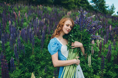 Red-haired girl in blue dress with lupines. Red-haired woman in blue dress with lupines Stock Photography
