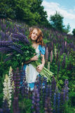 Red-haired girl in blue dress with lupines. Red-haired woman in blue dress with lupines Royalty Free Stock Image