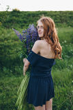 Red-haired girl in blue dress with lupines. Red-haired woman in blue dress with lupines Stock Images