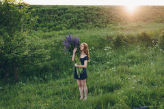 Red-haired girl in blue dress with lupines. Red-haired woman in blue dress with lupines Royalty Free Stock Photos