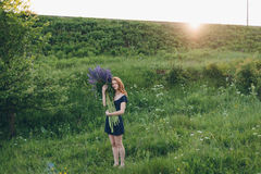 Red-haired girl in blue dress with lupines. Red-haired woman in blue dress with lupines Stock Photos