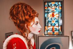 Red-haired girl with blue eyes in red dress. Queen with a high hairdo. Vintage image. A woman with pale skin royalty free stock photography