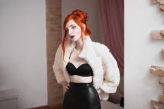 Red-haired girl with blue eyes and red lips in luxurious white fur coat. And black skirtwoman with earrings and a heart on her cheek, luxurious femme fatale Royalty Free Stock Image