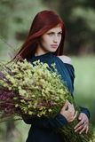 Red-haired girl with a bouquet of wild flowers. Red-haired girl holding a bouquet of wild flowers royalty free stock photography