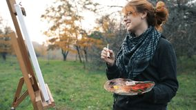 Red-haired girl with a bun painting a picture on an easel in nature, a young woman involved in creativity and enjoying beautiful l stock video