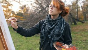 Red-haired girl with a bun painting a picture on an easel in nature, a young woman involved in creativity and enjoying beautiful l stock video footage