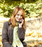 Red-haired girl calling by the phone Stock Image