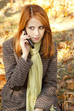 Red-haired girl calling by the phone Royalty Free Stock Image