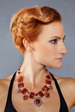 Red-haired girl with cheekbones. Young beautiful red-haired girl with chiseled cheekbones in designer jewelry Royalty Free Stock Images