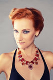Red-haired girl with chiseled cheekbones. Young beautiful red-haired girl with chiseled cheekbones in designer jewelry Royalty Free Stock Photography