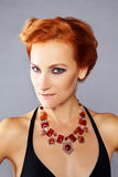 Red-haired girl with chiseled cheekbones. Young beautiful red-haired girl with chiseled cheekbones in designer jewelry Royalty Free Stock Image