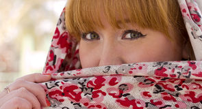 The red-haired girl closes half of his face with a scarf. Stock Photo